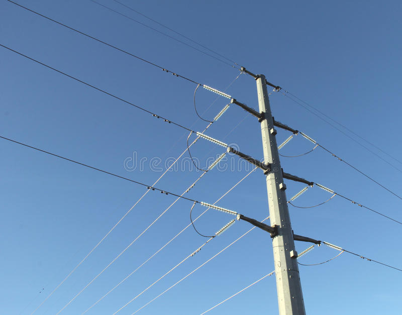 High voltage power line. Metal high voltage power line against a blue sky background stock images