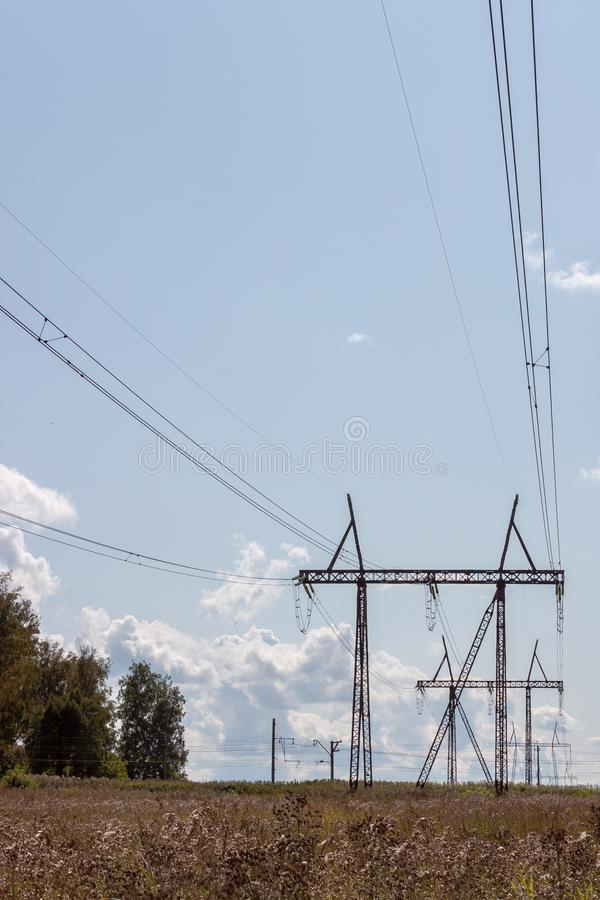 High voltage power line and pylons on a sunny day against the blue sky with clouds royalty free stock image