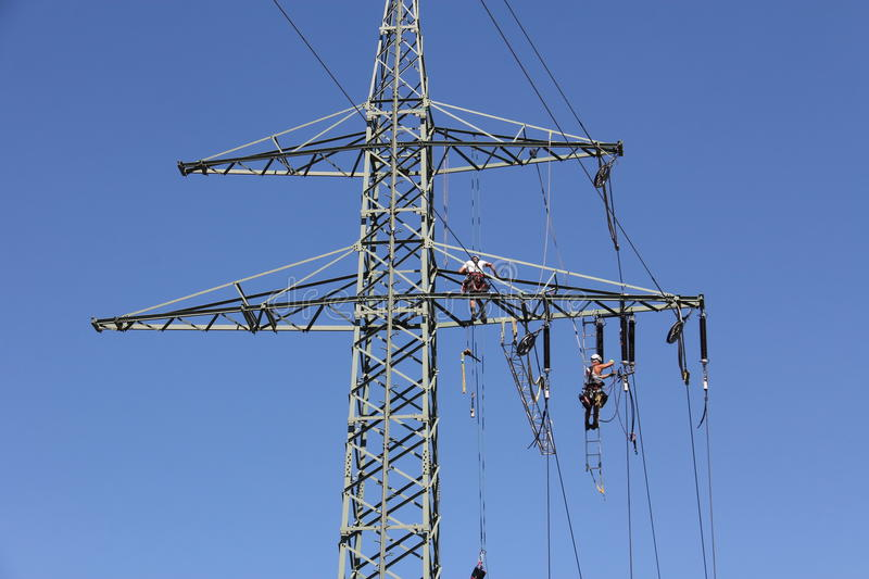 High voltage power line. Workers assemble a new high-voltage line stock image