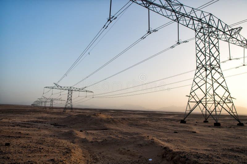 High voltage power lines in desert valley stock photo