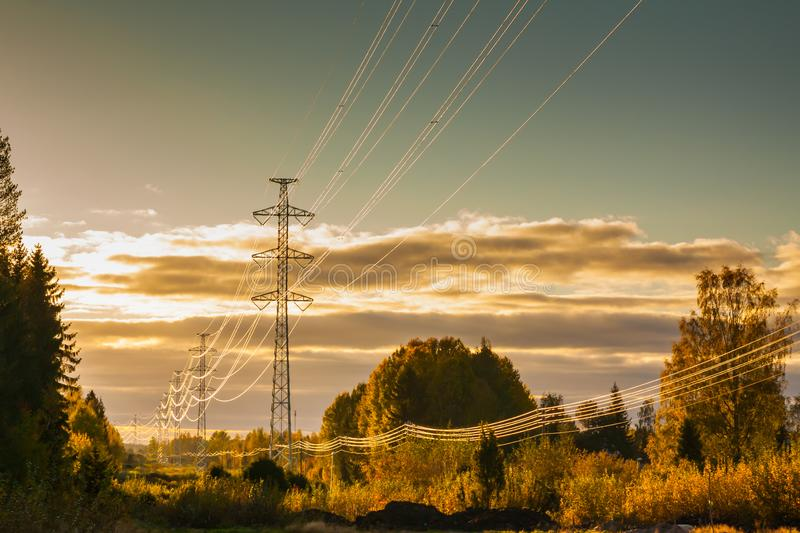 High-voltage power lines at golden sunset at autumn in Finland.  stock photography
