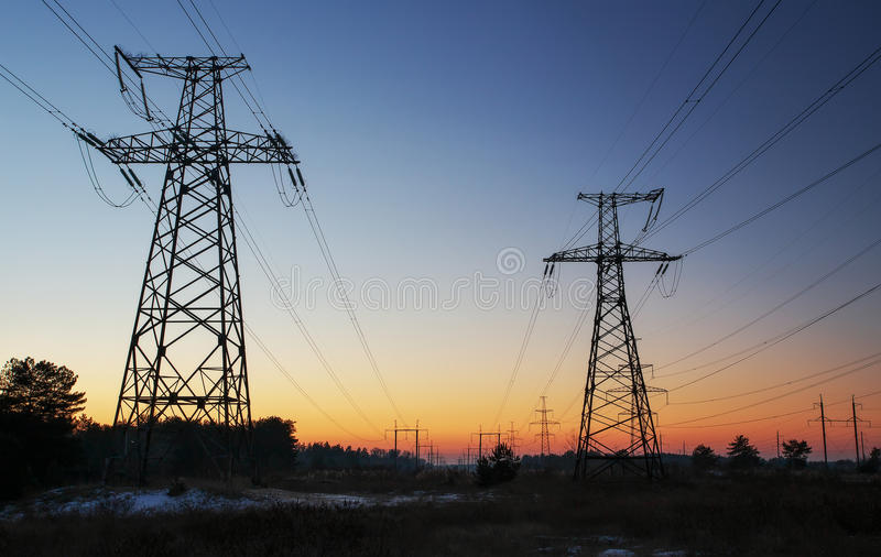 High-voltage power lines during sunrise royalty free stock image