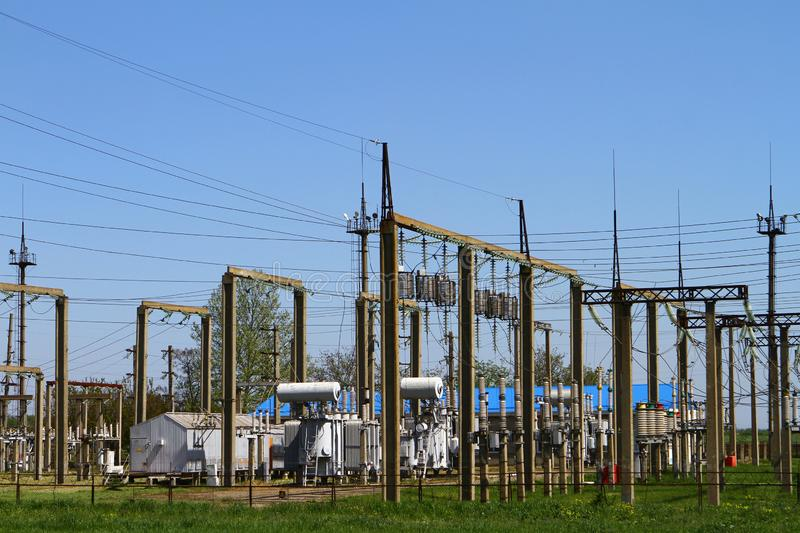 High-voltage power lines and voltage transformer blocks on a blue sky. Electric power substation stock photos