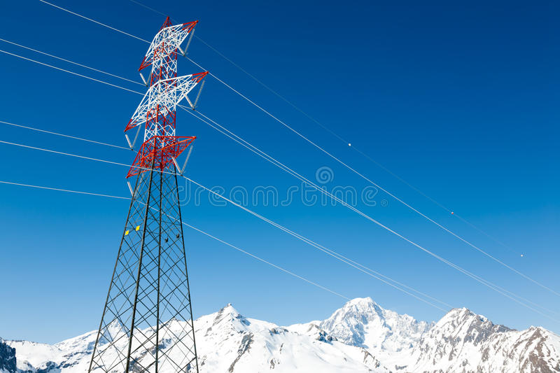 High voltage power lines in winter mountain landscape stock image