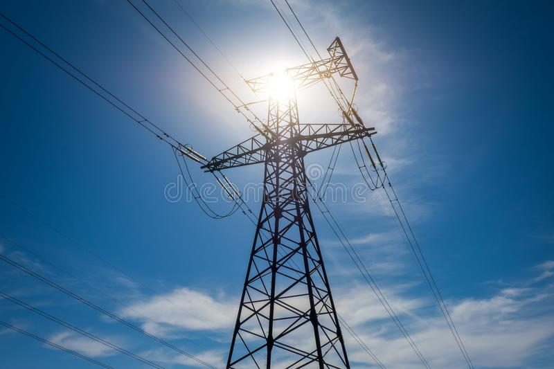A high voltage power pylons against blue sky royalty free stock image