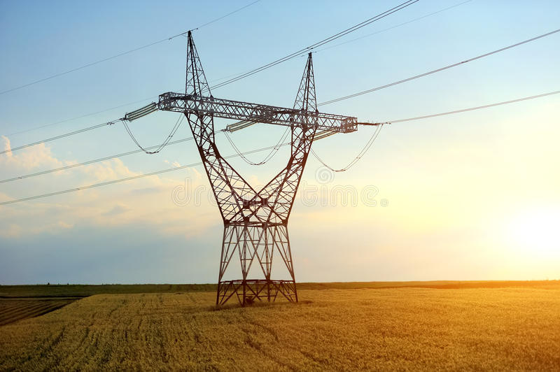 High voltage pylon. High voltage line with electricity pylons surrounded by cultivated field stock photo