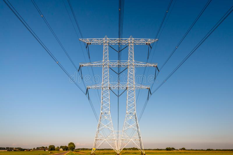 High voltage pylons against a blue sky. Colorful rural Dutch landscape with high voltage pylons and lines against a blue sky. It is a sunny evening in summertime stock photo