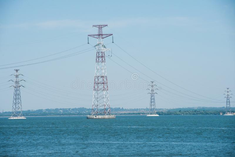 High-voltage pylons of power lines on the river royalty free stock image