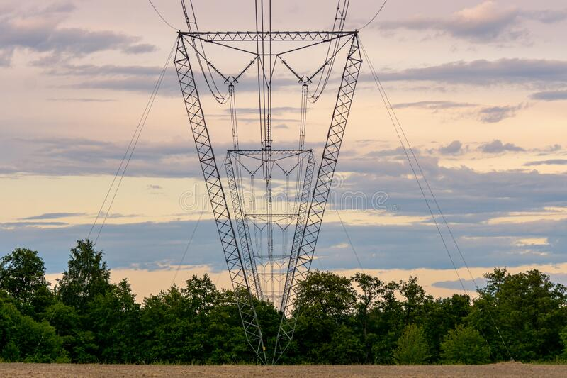 High voltage pylons standing in a diminishing perspective. Several high voltage pylons or towers standing in a row in a diminishing perspective, getting smaller stock images
