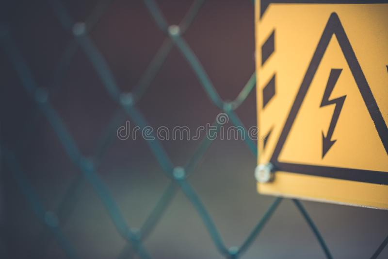 High voltage danger electricity sign on fence, yellow danger sign stock photography