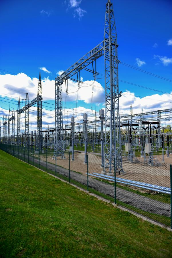 High-voltage tower on green grass and sky in background. - Image.  royalty free stock photo