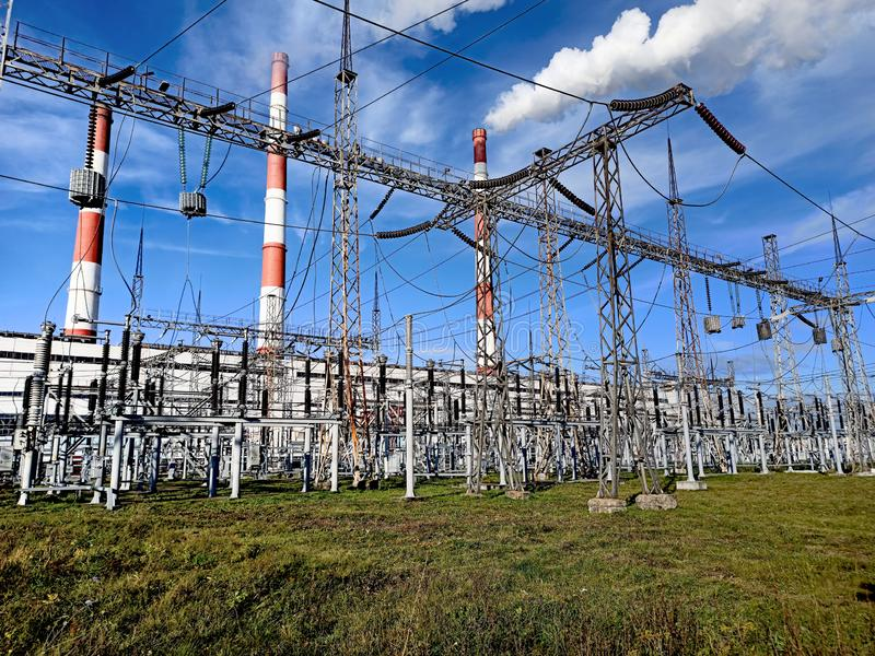 High-voltage towers on a background of blue sky and green grass. Red and white pipe with steam from a power plant stock image