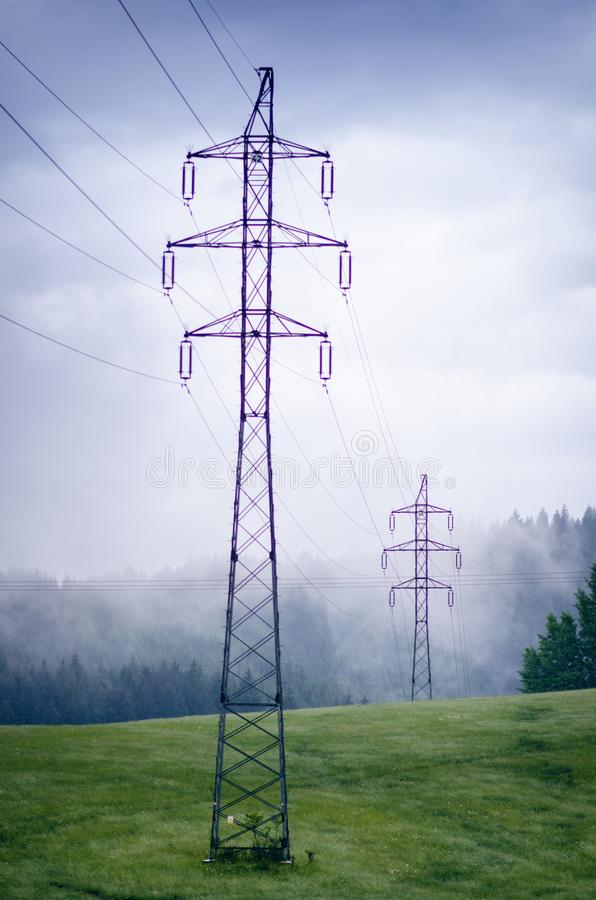 High voltage towers in a middle of forests and meadow. Electricity pylon with dark atmosphere in a nature. Rainy day. Power transm stock image