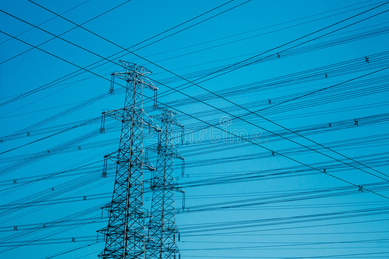 High-voltage towers silhouetted against blue stock photos