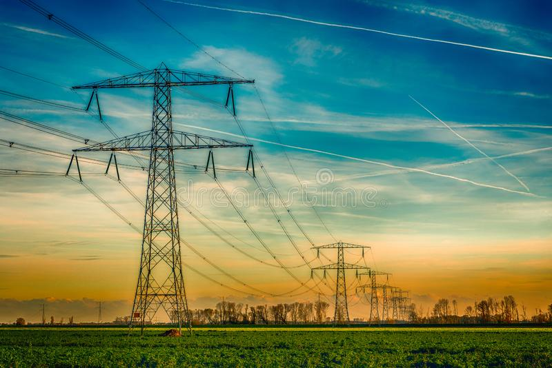 High voltage towers with thick hanging power cables in a rural l. Overview of power pylons and high voltage lines in a long row in a rural landscape. The photo stock image