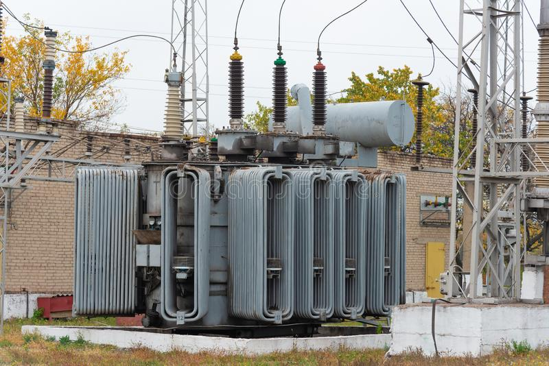 High voltage transformer at an electrical substation of the city power grid. Power wires with high voltage royalty free stock image