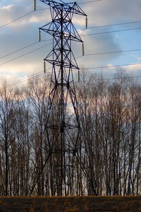 High-voltage transmission line in the spring forest at sunset against the background of the April blue sky with light clouds. Silhouettes of trees in the royalty free stock images