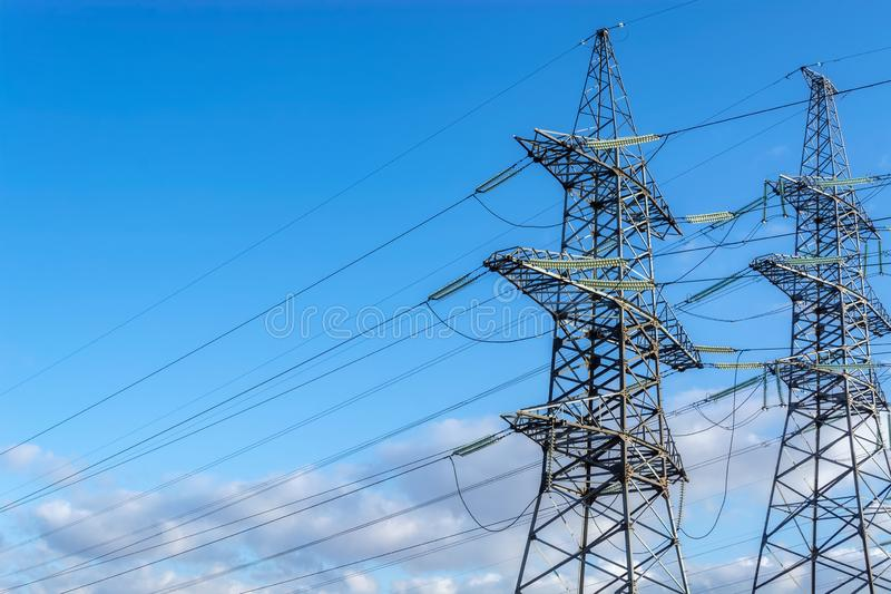 High-voltage transmission line. Two supports of high-voltage transmission line with electric power wires on the blue sky background royalty free stock photography