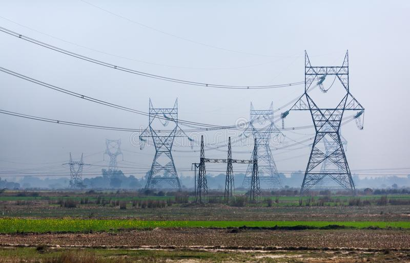High voltage transmission towers line as gigantic owls royalty free stock photography
