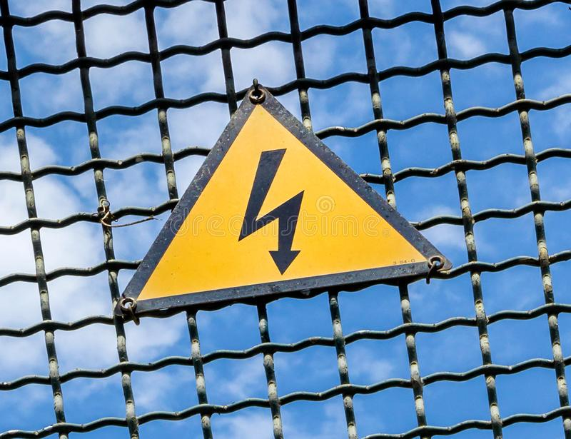High voltage warning sign. Electrical hazard sign placed on a metal fence stock images
