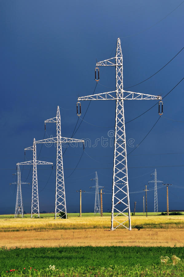 High voltage wires. High voltage pillars and lines surrounded by stormy clouds royalty free stock images