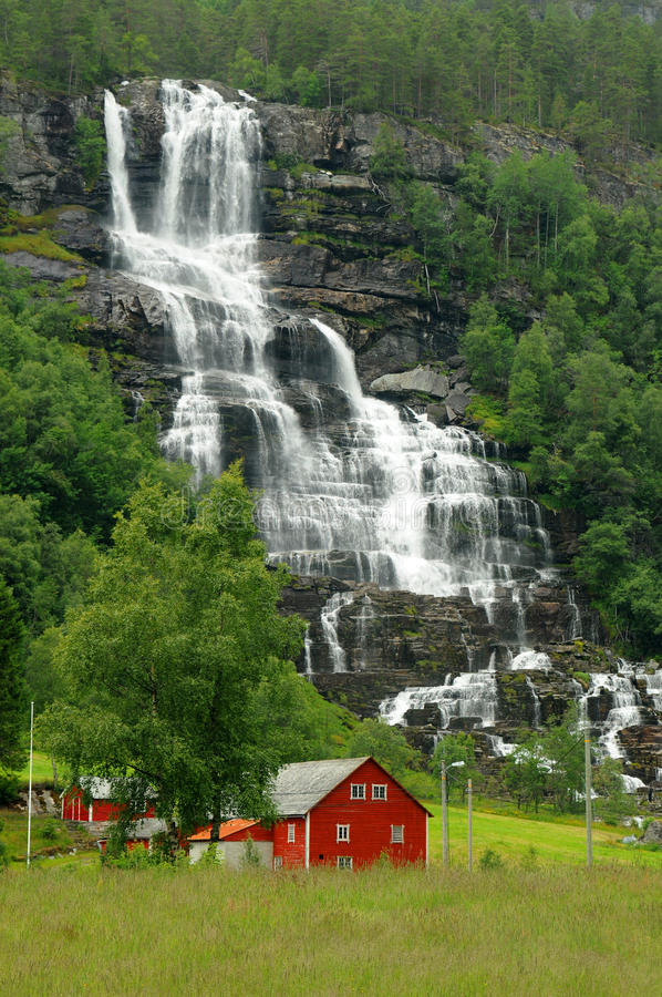 High waterfall in countryside. Scenic view of high waterfall in countryside with traditional red painted houses in foreground, Norway stock photos