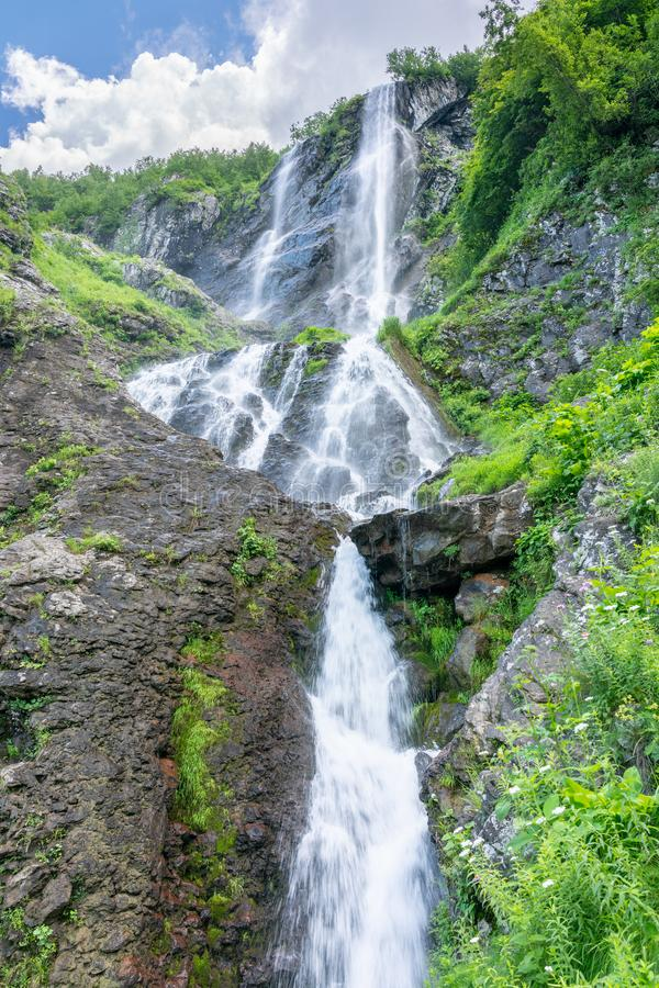 High waterfall with a powerful stream falling from a cliff royalty free stock images