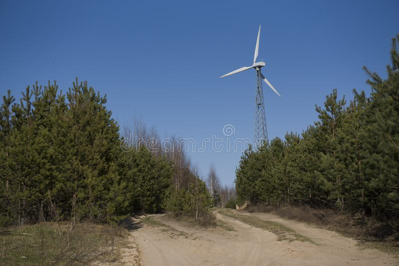 High windmill on the edge of the forest stock image