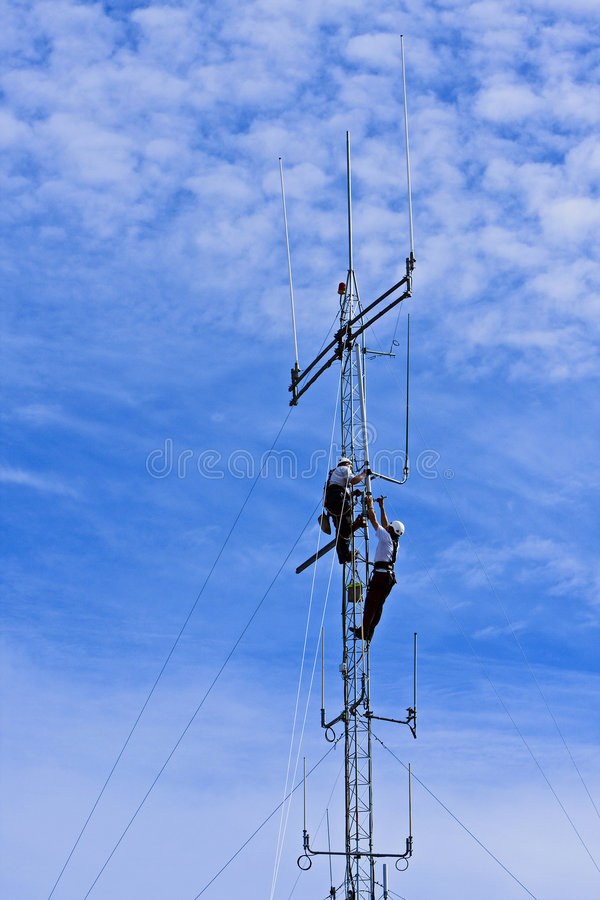 High Workers. Two men working high at the sky on an antenna pole stock photography