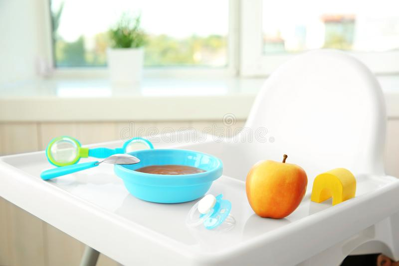 Highchair avec l'aliment pour bébé sain à la maison photographie stock libre de droits