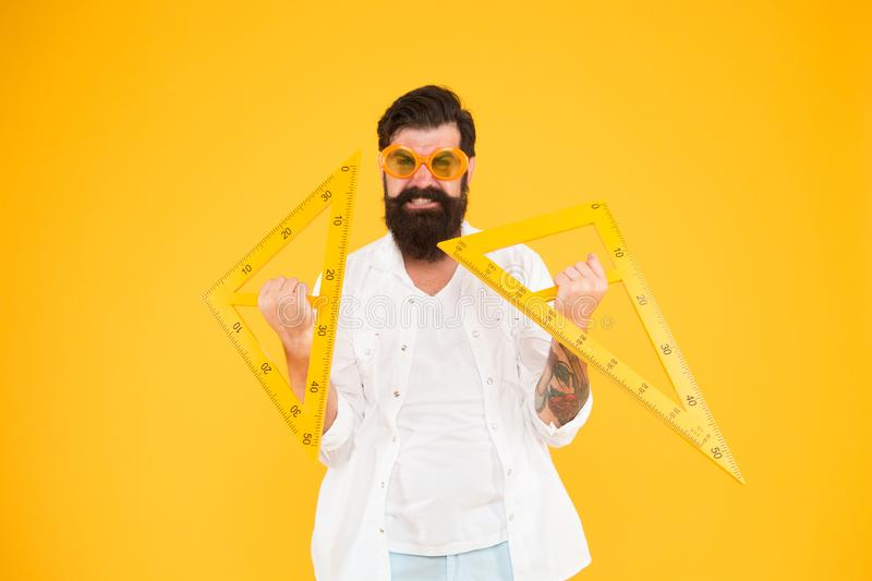 Higher education begins here. University professor holding triangles on yellow background. Bearded man preparing for. University studies. University of royalty free stock images
