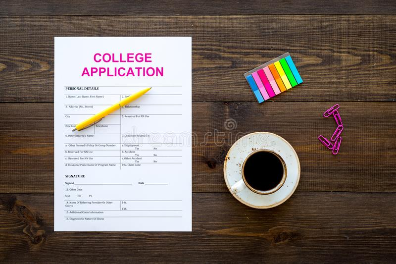 Higher education. College application form ready to fill near coffee cup and stationery on dark wooden background top. View stock image