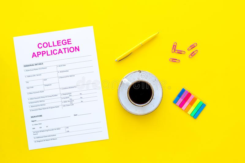 Higher education. College application form ready to fill near coffee cup and stationery on yellow background top view.  royalty free stock images