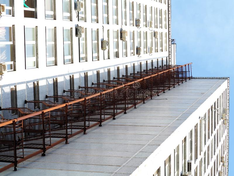 Higher escape. Fire escape ladder goes all the way up on the side of high-rise building royalty free stock photos