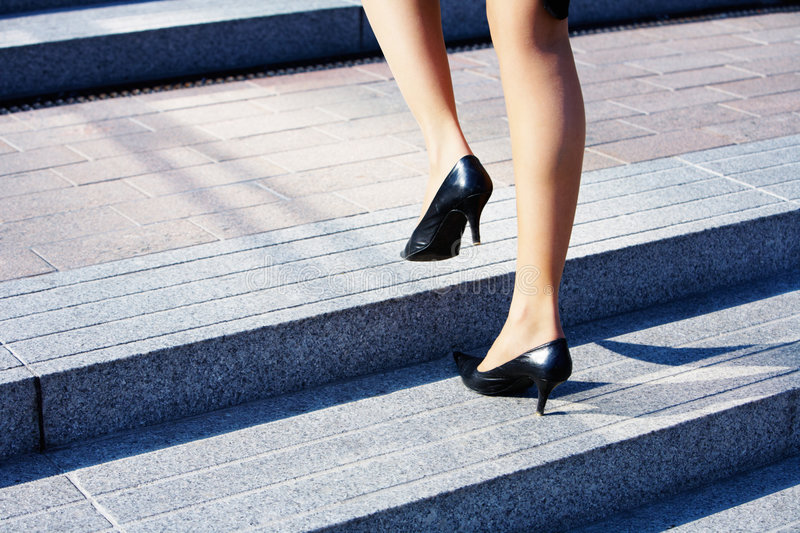 Higher Level. Businesswoman taking step to higher level on stairway royalty free stock photography