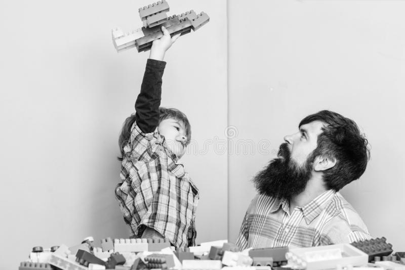 Higher means better. happy family leisure. small boy with dad playing together. child development. building plane with. Constructor. father and son play game royalty free stock photo