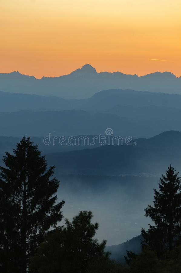 The highest peak of Julian Alps on orange sky with silhouette of spruce treetops in foreground stock photos
