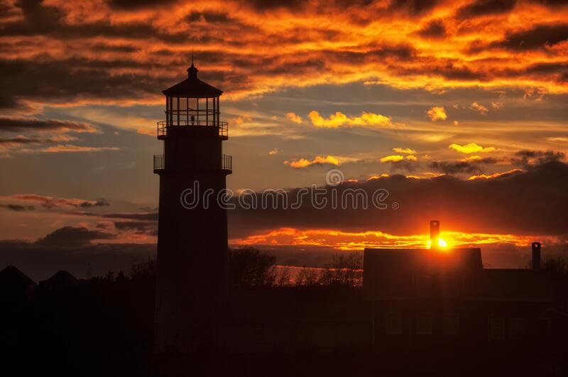 Highland Lighthouse Cape Cod Dramatic sunset. The silhouette of the highland lighthouse in north truro massachusetts on cape cod against a dramatic orange sunset stock photos