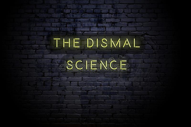 Highlighted brick wall with neon inscription the dismal science royalty free stock images