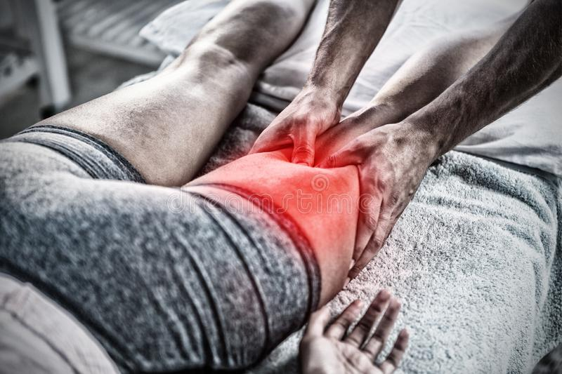 Composite image of highlighted pain. Highlighted pain against physiotherapist giving leg massage to a woman royalty free stock image