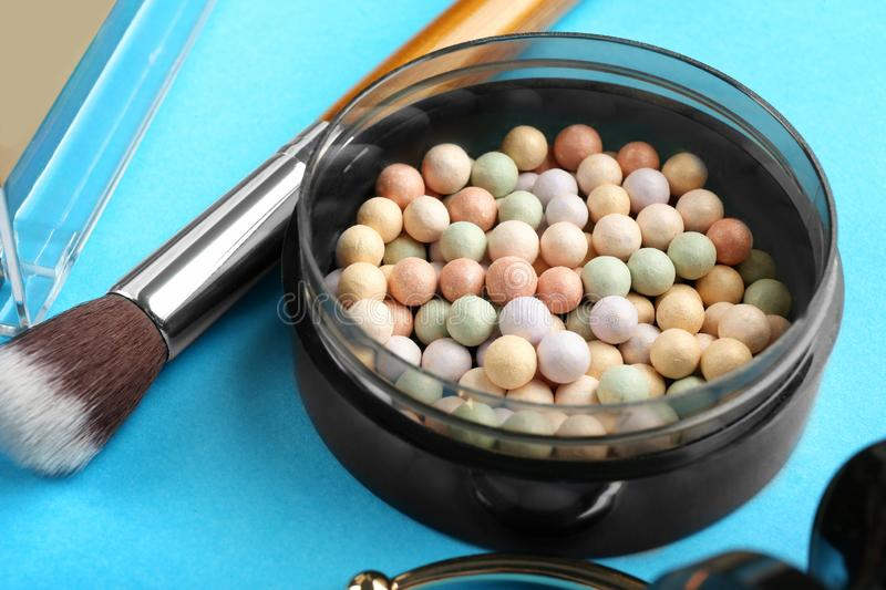 Highlighter pearls and makeup brush on color background. Decorative cosmetics stock photography