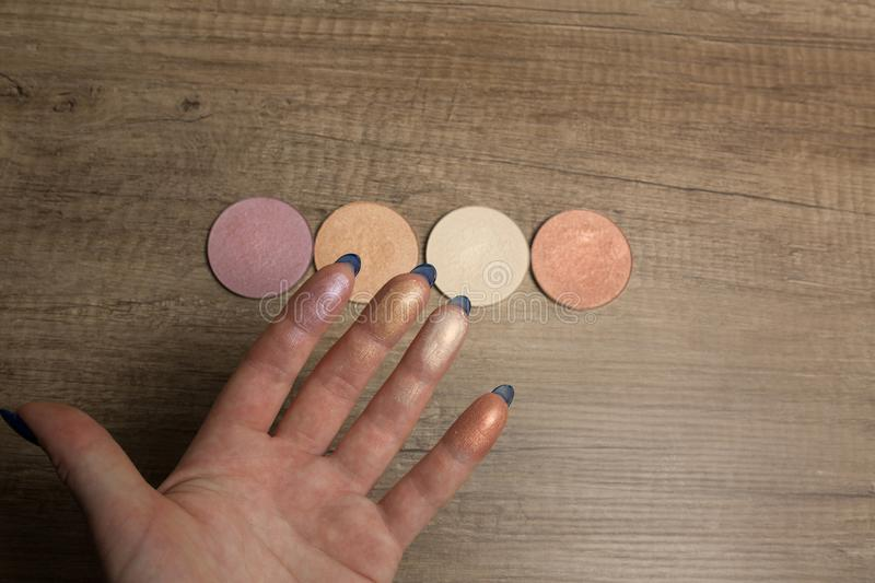 Highlighter swatches on a female hand on a wood background. Closeup royalty free stock photography