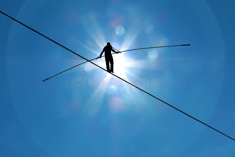 Highline walker in blue sky concept of risk taking and challenge. Tightrope walker balancing on the rope concept of risk taking and challenge stock photos