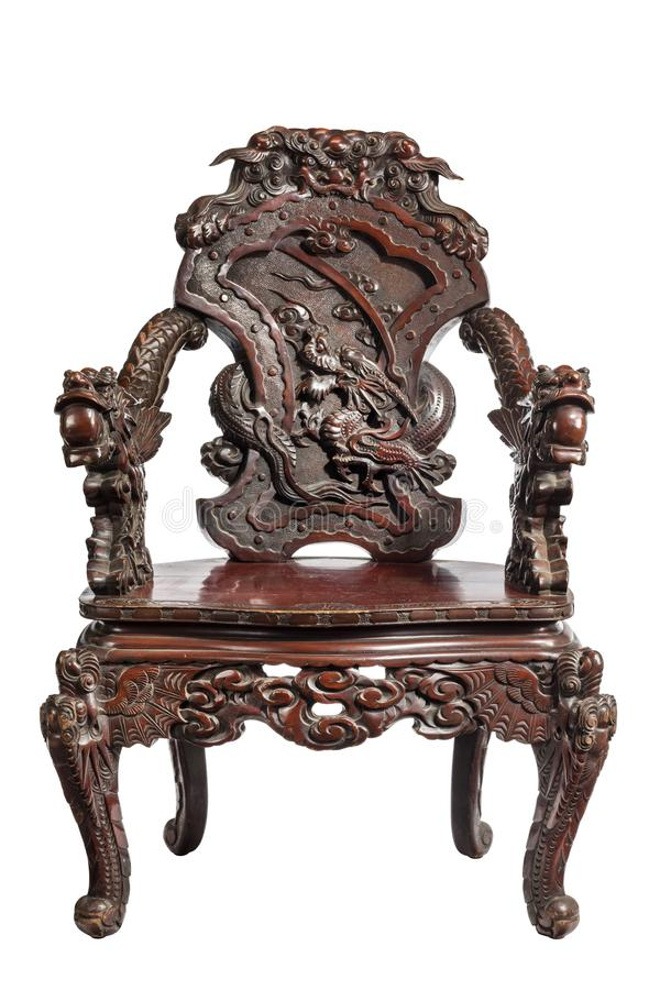 Chinese hardwood armchair with  carved with openwork designs. Highly carved Chinese rosewood arm chair, the arched back with relief carved dragon, curving arms royalty free stock photo