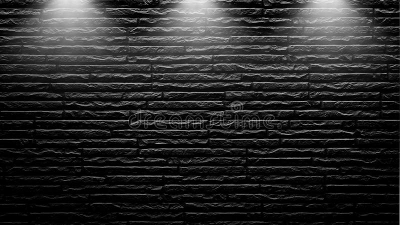 Highly contrasted spotlights on an outdoor black brick wall.  royalty free stock image