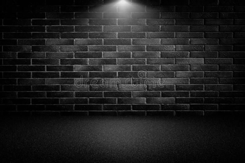 Highly contrasted spotlights on an outdoor black brick wall.  royalty free stock photo