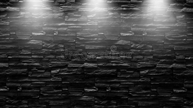 Highly contrasted spotlights on an outdoor black brick wall.  stock photo