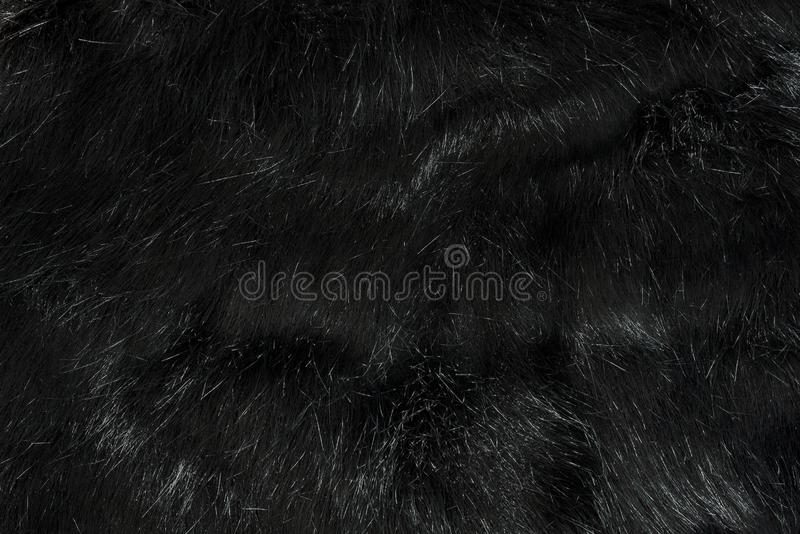 Highly detailed background texture of black fur made of synthetic animal long hair. royalty free stock photos