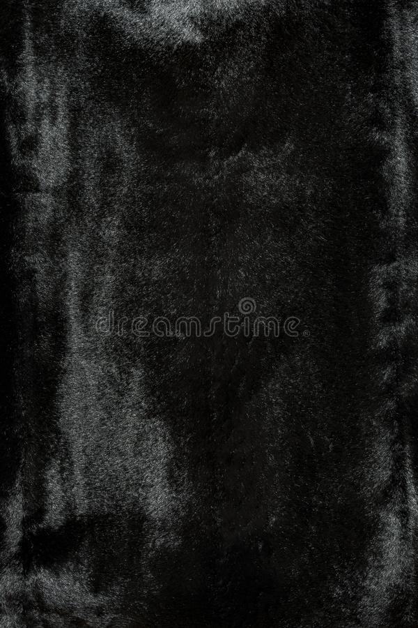 Highly detailed background texture of black fur made of synthetic animal short hair. stock photo
