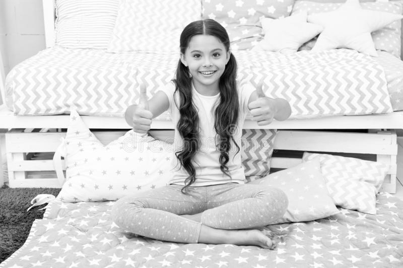 Highly recommend. Girl child sit near bed. Kid prepare to go to bed. Pleasant time in cozy bedroom. Girl kid long hair. Cute pajamas shows thumbs up gesture stock photography